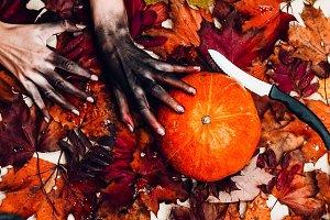 hands of a corpse climb on a pumpkin