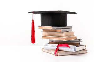 Academic cap on stack of books isola