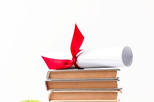 Diploma on pile of books and apple i