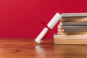 Diploma and stack of different books
