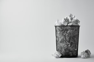 office trash bin with crumpled paper