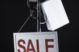 sale signboard and paper bag on coat