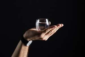 cropped shot of man holding glass of