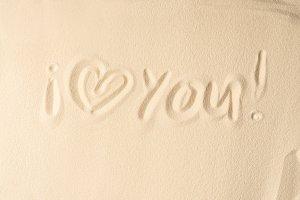 I love you inscription on light sand