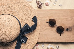 Straw hat with sunglasses on wooden