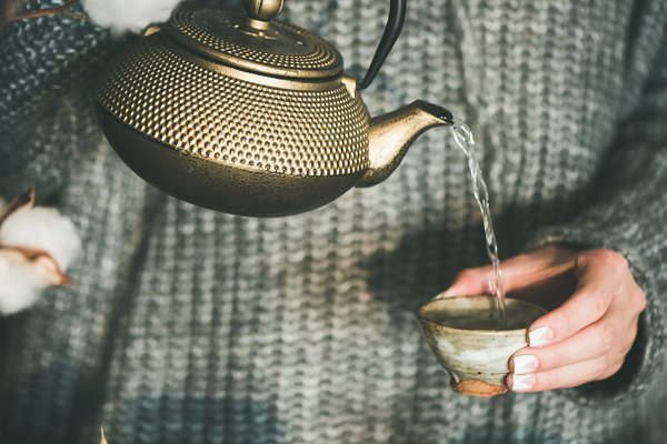 Woman pouring tea from golden pot