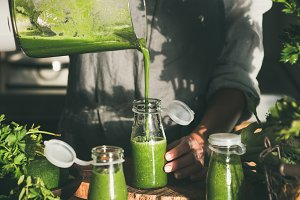 Young female pouring green smoothie