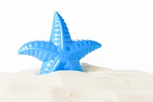 Toy starfish in sand isolated on whi