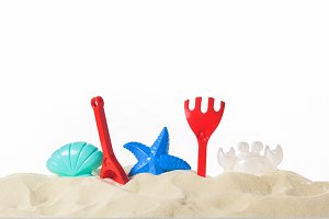 Plastic beach toys in sand isolated