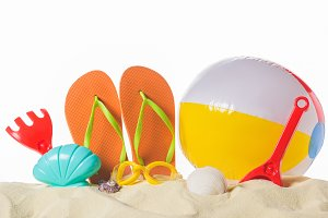 Beach ball and flip flops in sand is