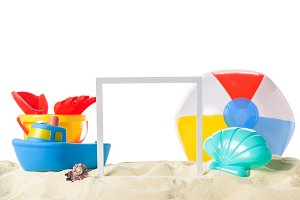 Beach toys and frame in sand isolate