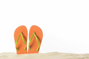 Pair of flip flops in sand isolated