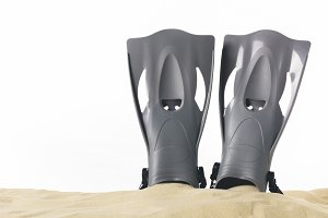 Black flippers in sand isolated on w