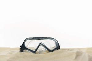 Diving mask in sand isolated on whit