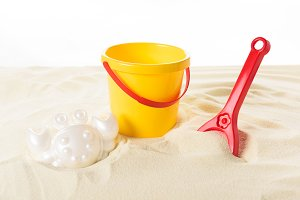 Bucket and plastic toys in sand isol