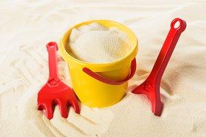 Bucket and plastic toys on sandy bea