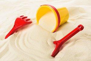 Kids toys and bucket on sandy beach