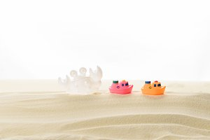 Toy boats and crab in sand isolated