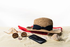 Straw hat on towel and sunglasses wi