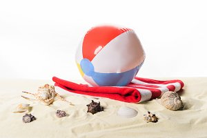 Beach ball on towel by seashells in
