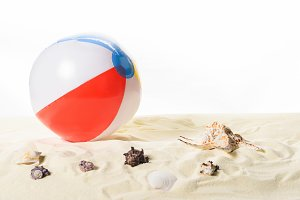 Beach ball with seashells in sand is