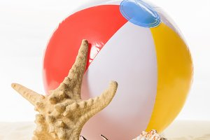Beach ball and starfish in sand isol