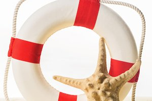 Life ring and starfish in sand isola
