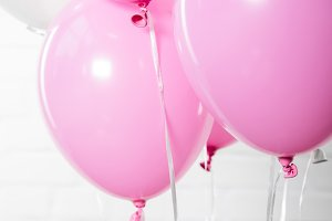 Shiny white and pink balloons on whi