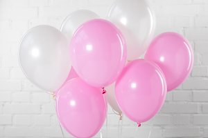 Pink and white party balloons on whi