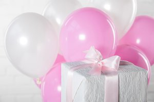Gift box and balloons on white brick
