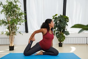 Pregnant woman doing yoga indoors