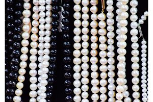 White and black pearls on a black