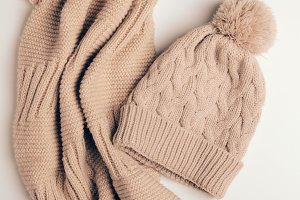 Knitted scarf and a beige cap