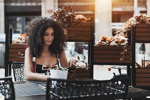 Cute curly female in an outdoor cafe