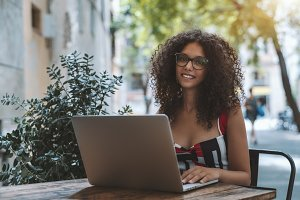 Smiling curly woman with the netbook