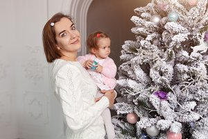 Mom with a little girl decorate a Ch