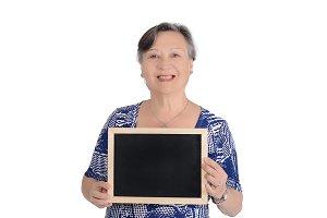 Elderly woman holding empty chalkboa