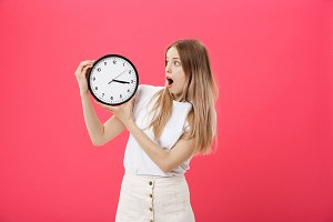 Amazed woman holding clock