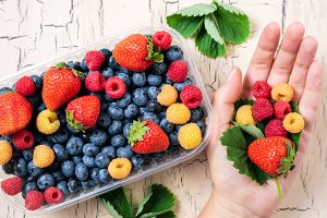 Female hand hold fresh berries