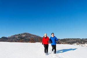 Senior couple jogging in snowy
