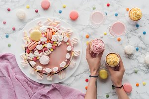 cropped view of hands with cupcakes