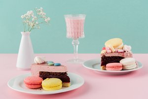 macaroons and pieces of cake on plat