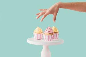 cropped view of woman taking cupcake