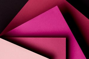 Paper sheets in pink tones on black