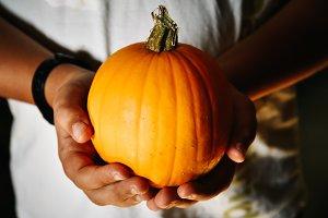Child hands holding a pumpkin