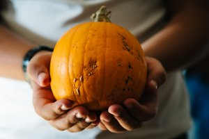 Child hands holding a pumpkin