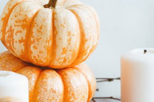 Small pumpkins and white candles