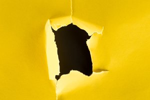 close-up shot of hole in yellow pape