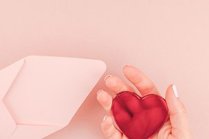 Woman hand holding small pink love l