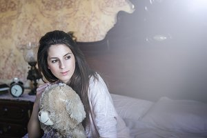 woman sitting on bed with a teddy